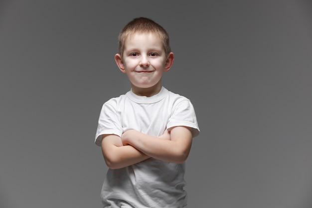 Portret van gelukkige kleine jongen in wit t-shirt glimlachend op grijze achtergrond camera kijken in studio omgeving. portret van modieus mannelijk kind.