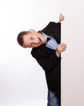 Portret van gelukkige kleine jongen met witte die spatie op witte achtergrond wordt geïsoleerd
