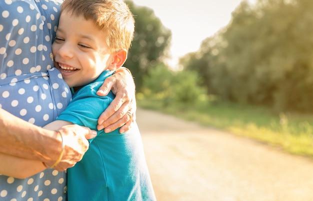Portret van gelukkige kleinzoon die grootmoeder omhelst over een natuur buiten achtergrond