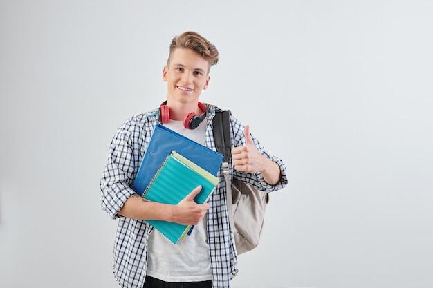 Portret van gelukkige knappe jonge middelbare schoolstudent met handboeken die thumbs-up tonen en vooraan glimlachen