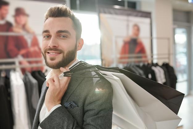 Portret van gelukkige knappe jonge zakenman met boodschappentassen op schouder tijdens het winkelen in winkelcentrum