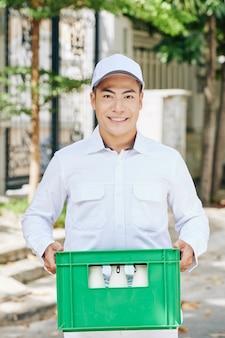 Portret van gelukkige knappe vietnamese melkboer die groen plastic melkkrat draagt