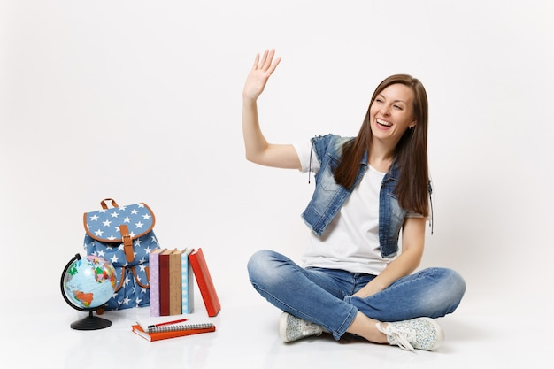 Portret van gelukkige lachende vrouw in denim kleding student zwaaiende hand voor groet zitten in de buurt van globe, rugzak schoolboeken geïsoleerd op een witte muur