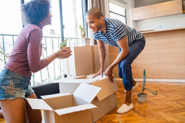 Portret van gelukkige latijnse paar die kartondoos inpakken om in nieuw appartement te verhuizen. onroerend goed concept.