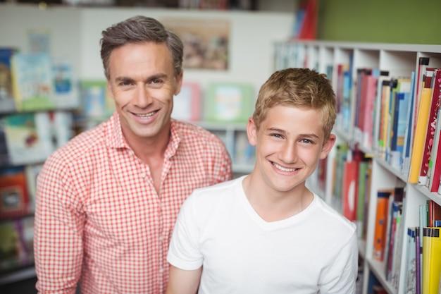 Portret van gelukkige leraar en student in bibliotheek