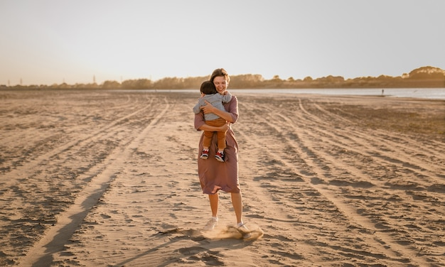 Portret van gelukkige liefdevolle moeder haar zoontje knuffelen in het zonnige park in de buurt van de rivier