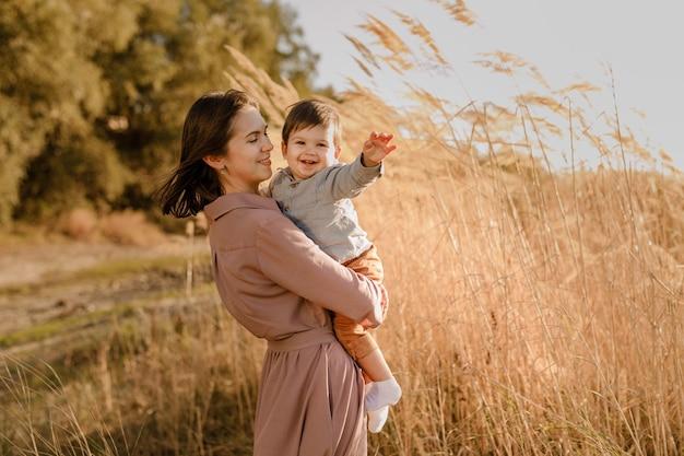 Portret van gelukkige liefdevolle moeder haar zoontje knuffelen in het zonnige park in de buurt van de rivier.