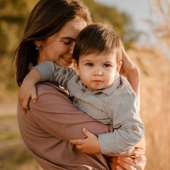 Portret van gelukkige liefdevolle moeder haar zoontje knuffelen