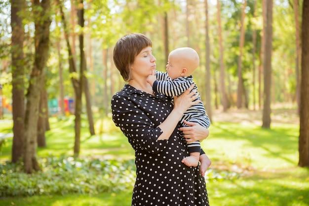Portret van gelukkige liefhebbende moeder en haar baby buitenshuis