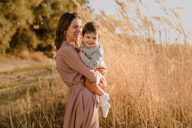 Portret van gelukkige liefhebbende moeder en haar zoontje buitenshuis.