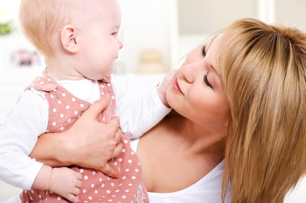 Portret van gelukkige liefhebbende moeder met baby thuis