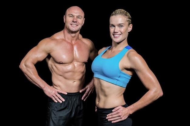 Portret van gelukkige man en vrouw met hand op heup