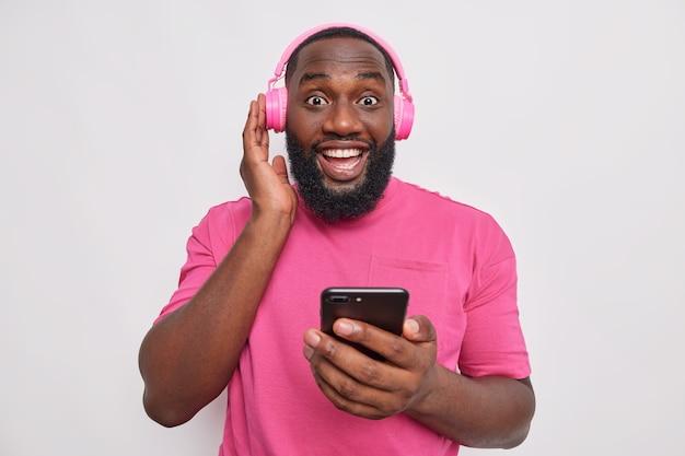 Portret van gelukkige man houdt hand op stereo hoofdtelefoon houdt mobiele telefoon luistert naar muziek draagt casual roze t-shirt geïsoleerd over witte muur
