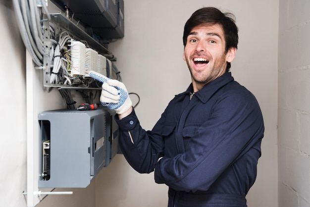 Portret van gelukkige mannelijke elektricien die op kringsraad richten