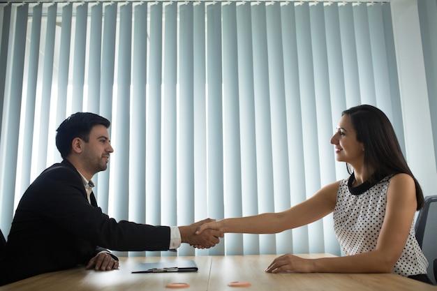 Portret van gelukkige mannelijke en vrouwelijke partners handen schudden