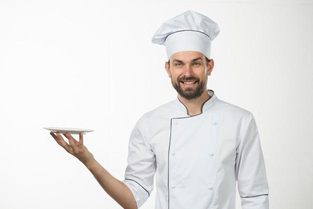 Portret van gelukkige mannelijke kok die een witte schotel in zijn hand houdt
