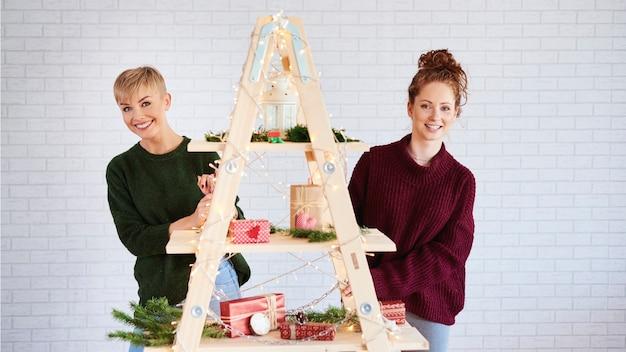 Portret van gelukkige meisjes die de kerstboom versieren