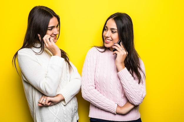 Portret van gelukkige meisjes die op mobiele telefoons spreken die over gele muur worden geïsoleerd