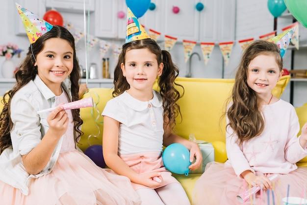 Portret van gelukkige meisjes met ballon en feest hoorn zittend op de bank