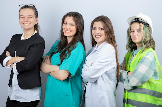 Portret van gelukkige mensen van verschillende beroepen staande armen gekruist op witte achtergrond. hoge kwaliteit foto