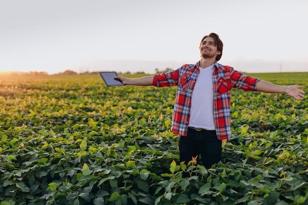 Portret van gelukkige mensenlandbouwkundige die zich op een gebied met apart handen bevinden