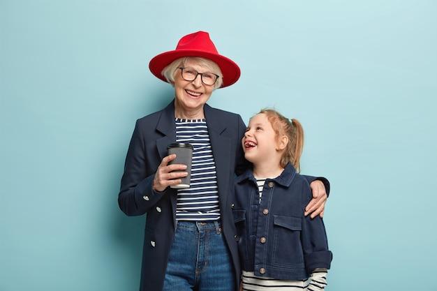 Portret van gelukkige modieuze oma en klein schattig kind brengen vrije tijd samen door, drinken afhaalkoffie, knuffelen, hebben vriendschappelijke relaties, dragen denimkleding, staan over blauwe muur.