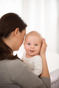Portret van gelukkige moeder en baby, ouder en klein kind thuis ontspannen