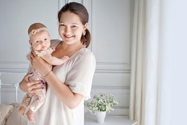 Portret van gelukkige moeder en baby thuis. kopieer ruimte