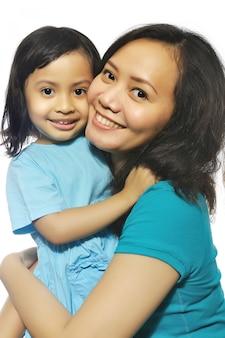 Portret van gelukkige moeder en dochter die over witte achtergrond wordt geïsoleerd