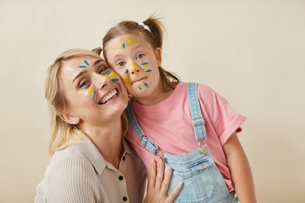 Portret van gelukkige moeder en dochter met geschilderde gezichten die elkaar omhelzen en bij camera glimlachen tegen de witte achtergrond