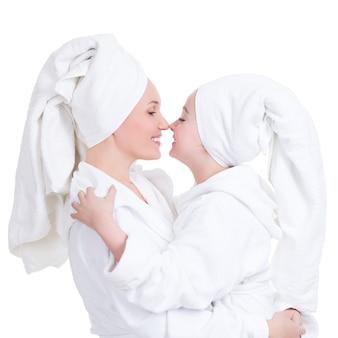 Portret van gelukkige moeder en jonge dochter in witte peignoir bekijken elkaar - geïsoleerd