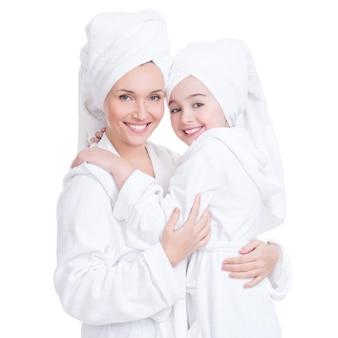 Portret van gelukkige moeder en jonge dochter in witte peignoir en geïsoleerde handdoek. gelukkig gezin mensen concept.