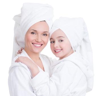 Portret van gelukkige moeder en jonge dochter in witte peignoir en geïsoleerde handdoek