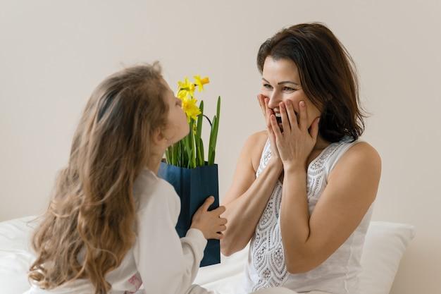 Portret van gelukkige moeder en kleine dochter, meisje feliciteert moeder met boeket bloemen.