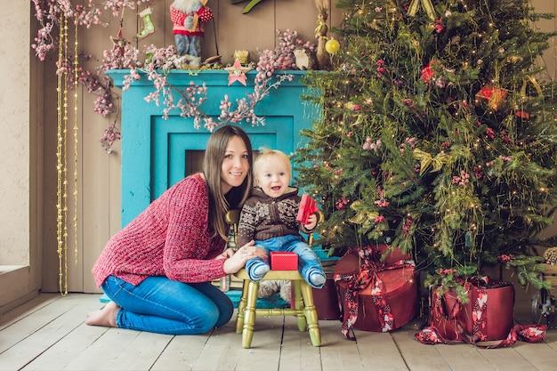 Portret van gelukkige moeder en schattige baby vieren kerstmis. nieuwjaars vakantie. peuter met