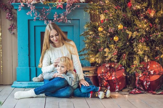 Portret van gelukkige moeder en schattige jongen, kerstmis vieren. peuter met moeder
