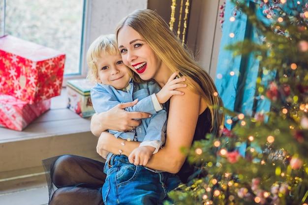 Portret van gelukkige moeder en schattige jongen vieren kerstmis. nieuwjaars vakantie. peuter met moeder