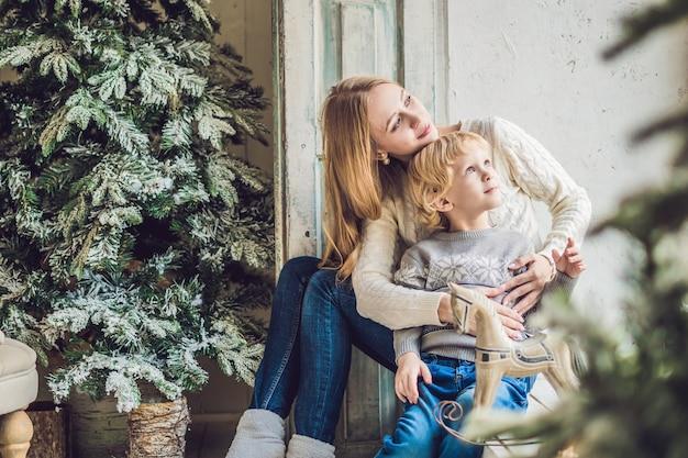 Portret van gelukkige moeder en schattige jongen vieren kerstmis. nieuwjaars vakantie
