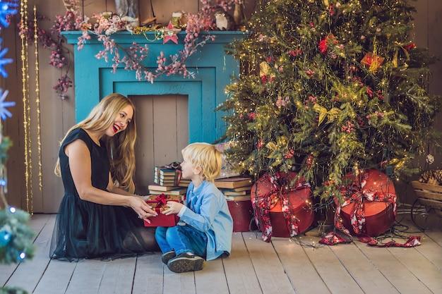 Portret van gelukkige moeder en schattige jongen vieren kerstmis