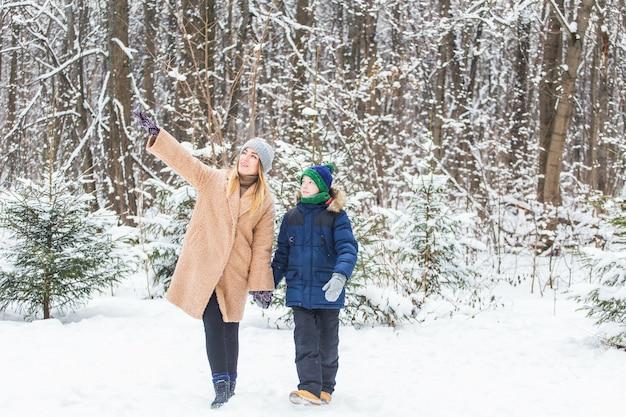 Portret van gelukkige moeder met kindzoon in de winter in openlucht