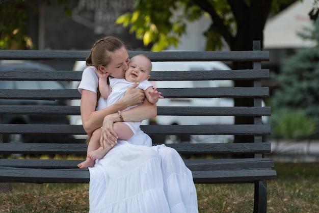Portret van gelukkige moeder met schattige kleine baby zittend op bankje in park.