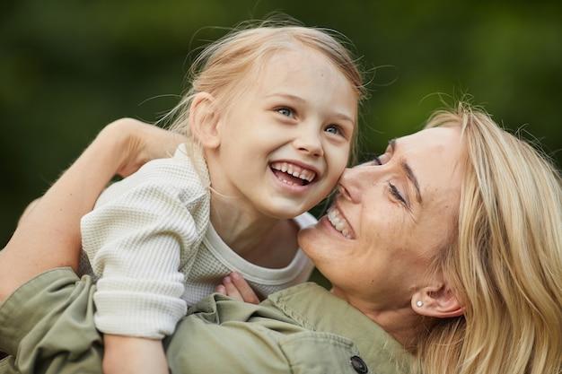 Portret van gelukkige moeder spelen met schattig klein meisje buitenshuis terwijl ze plezier hebben samen in park