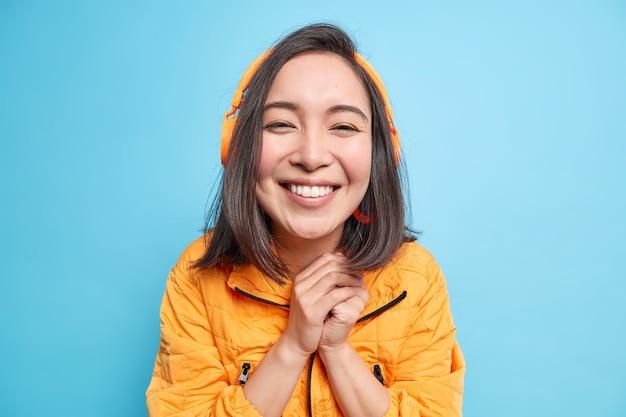 Portret van gelukkige mooie aziatische vrouw houdt handen bij elkaar glimlacht breed geniet van goed geluid met moderne headset luistert muziek uit afspeellijst draagt oranje jas geïsoleerd over blauwe muur