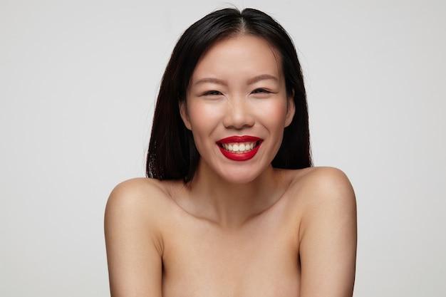 Portret van gelukkige mooie bruinogige jonge brunette vrouw die haar perfecte witte tanden toont terwijl ze breed lacht, in een hoge geest is terwijl ze over een witte muur staat