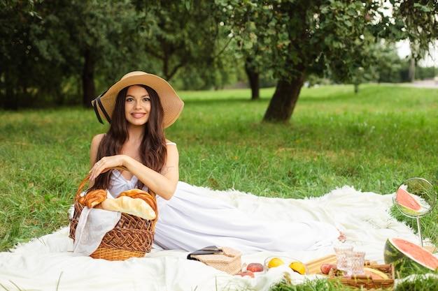 Portret van gelukkige mooie jonge dame in hoed die rust op picknick in park heeft terwijl een mand met brood in handen
