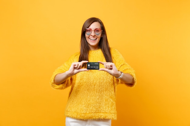 Portret van gelukkige mooie jonge vrouw in bont trui en hart bril met creditcard geïsoleerd op heldere gele achtergrond. mensen oprechte emoties, lifestyle concept. reclame gebied.