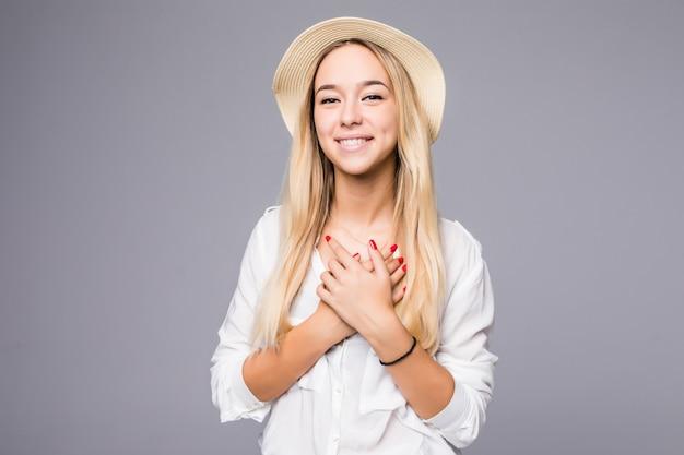 Portret van gelukkige mooie jonge vrouw in strooien hoed staat en legde handen op haar hart geïsoleerd over grijze muur