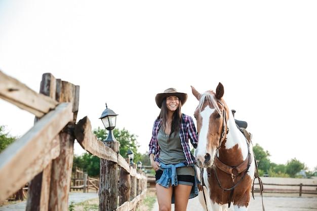 Portret van gelukkige mooie jonge vrouwenveedrijfster met haar paard op ranch