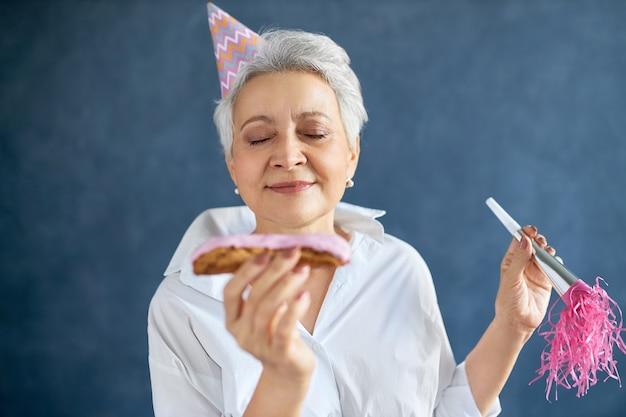 Portret van gelukkige mooie rijpe vrouw met grijs haar die de ogen gesloten houdt, gaat zoete smakelijke eclair proberen