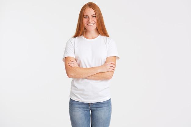Portret van gelukkige mooie roodharige jonge vrouw met lang haar en sproeten draagt t-shirt
